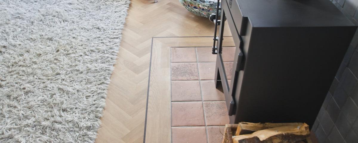 Visgraatvloer met band - open haard woonkamer - Vloerenbedrijf Bezema